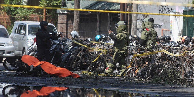 Members of police bomb squad inspect the wreckage of motorcycles at the site where an explosion went off outside a church in Surabaya, East Java, Indonesia, May 13, 2018.