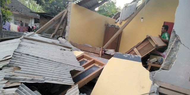 In this image made from video released by Indonesia's Disaster Mitigation Agency, a man inspects the damage caused by an early morning earthquake on the island of Lombok, Indonesia, Sunday, July 29, 2018