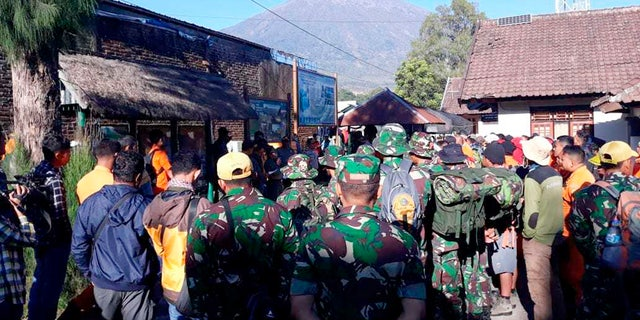 Indonesian soldiers and a rescue team gather to prepare for evacuating tourists from Mount Rinjani.