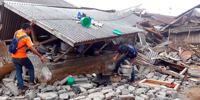 Villagers clear debris caused by an earthquake at Sajang village, Sembalun, East Lombok, Indonesia.