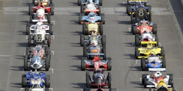 Cars from many eras lined up on the starting grid at Indianapolis Motor Speedway