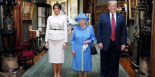 The queen poses for a photo with President Trump and Melania in the Grand Corridor during their visit to Windsor Castle