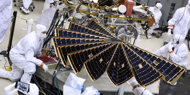 Technicians unfurl the InSight Mars lander's solar arrays during a key test at a Lockheed Martin Space Systems facility in Colorado on Jan. 23, 2018.
