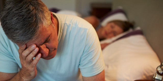 Man Awake In Bed Suffering With Insomnia Late At Night