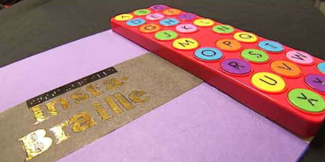 To use the Insta-Braille, a reader feels a Braille character, pushes the button, then hears the word of the alphabet it represents. (image: My Fox Atlanta)