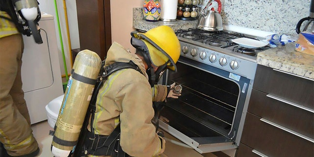 A firefighter examines a gas stove in the rented condo where an Iowa couple and their two children died in Tulum, Mexico.