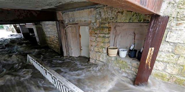 Floodwater pours into the basement of Schera's Algerian American Restaurant & Bar, in Elkader, Iowa, on Aug. 26, 2016. (Mike Burley/Telegraph Herald via AP)