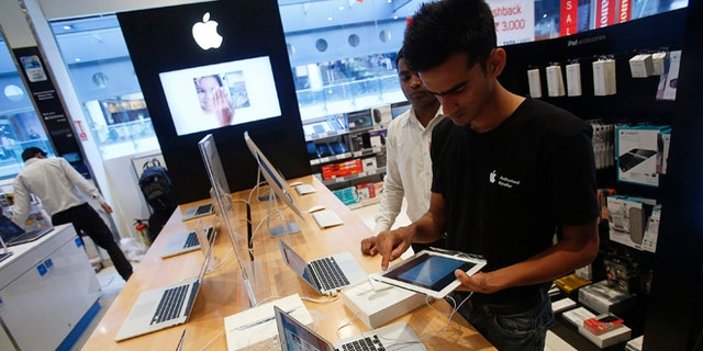 A salesperson unpacks an Apple iPad Mini to test it for a customer in the Apple specialty section of a Croma retail store in Mumbai February 22, 2013. The store offers Apple products including iPhones and iPads on instalment plans. More than four years after it started selling iPhones in India, Apple Inc is now aggressively pushing the iconic device through instalment payment plans that make it more affordable, a new distribution model and heavy marketing blitz. The result: iPhone shipments to India between October and December of 2012 nearly tripled to 250,000 units from 90,000 in the previous quarter, according to an estimate by Jessica Kwee, a Singapore-based analyst at consultancy Canalys. Picture taken February 22, 2013. REUTERS/Vivek Prakash (INDIA - Tags: BUSINESS SCIENCE TECHNOLOGY) - RTR3E840