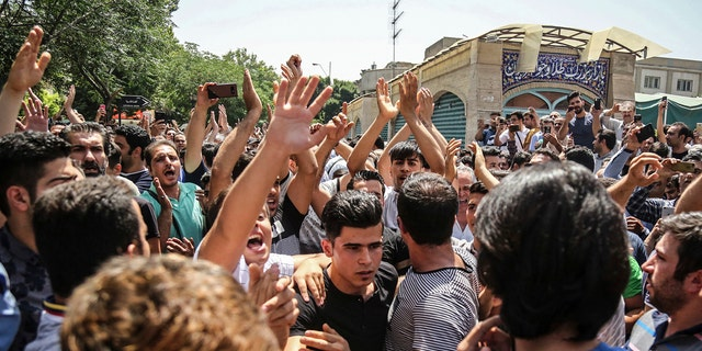 A group of protesters chant slogans at the main gate of old grand bazaar in Tehran, Iran, Monday, June 25, 2018.
