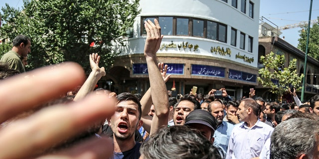 A group of protesters chant slogans at the main gate of old grand bazaar in Tehran, Iran, Monday, June 25, 2018