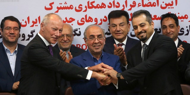 Chief Competitive Officer of Groupe Renault Thierry Bollor, left, Chairman of Industrial Development and Renovation Organization of Iran, IDRO, Mansour Moazami, center, and Negin Group CEO Kourosh Morshed Solouk join hands after signing a deal in Iran.