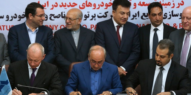 Chief Competitive Officer of Groupe Renault Thierry Bollor, left, Chairman of Industrial Development and Renovation Organization of Iran, IDRO, Mansour Moazami, center, and Negin Group CEO Kourosh Morshed Solouk sign a deal in Iran.