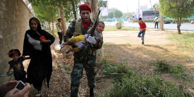 In this photo provided by Mehr News Agency, an Iranian army member carries away a child from a shooting scene during a military parade marking the 38th anniversary of Iraq's 1980 invasion of Iran, in the southwestern city of Ahvaz, Iran, Saturday, Sept. 22, 2018.