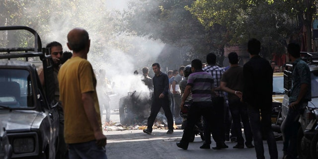 Oct. 3, 2012: This photo, taken by an individual not employed by the Associated Press and obtained by the AP outside Iran shows, Iranians stand in a street as a garbage can is set on fire, in central Tehran, near Tehran's old main bazaar.