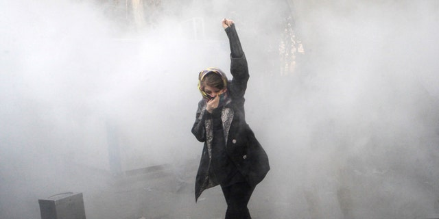 In this Saturday, Dec. 30, 2017 file photo, taken by an individual not employed by the Associated Press and obtained by the AP outside Iran, a university student attends a protest inside Tehran University while a smoke grenade is thrown by anti-riot Iranian police, in Tehran, Iran. (AP Photo, File)