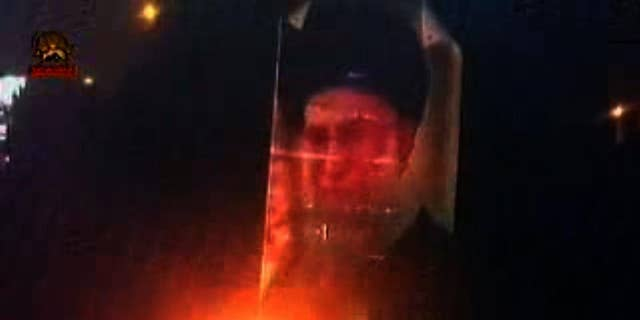 Photo of the Ayatollah is burned during recent protests in Iran.