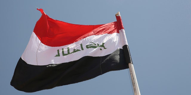 An Iraqi flag waves in the wind above the Iraqi Trebil border crossing.