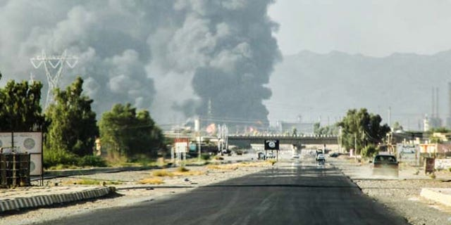 July 31, 2014: In this file photo, a column of smoke rises from an oil refinery in Beiji, some 155 miles north of Baghdad, Iraq, after an attack by Islamic militants. (AP)