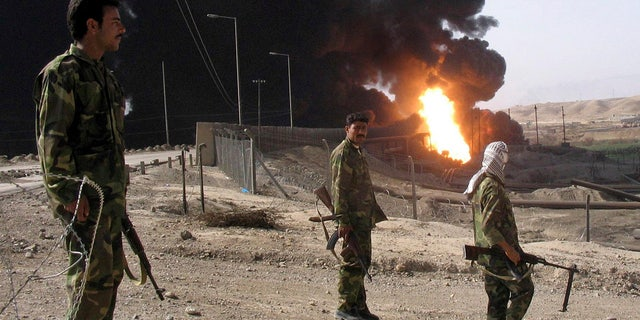 In this Oct. 12, 2005 file photo, Iraqi soldiers stand as an oil pipeline burns following an explosion in Beiji, Iraq.