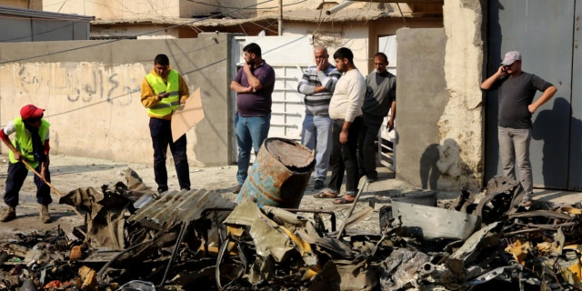 Jan. 15, 2014: Baghdad municipality workers clean up as civilians inspect the site of a car bomb attack near the Technology University in Sinaa Street in downtown Baghdad, Iraq.