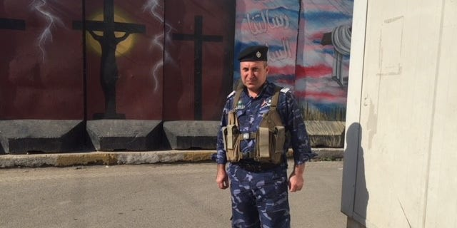 An armed security guard on duty outside a Christian church in Baghdad.