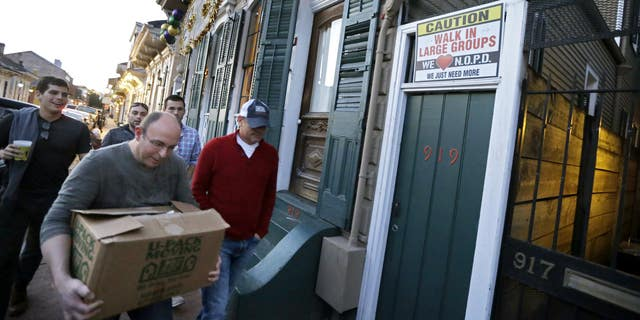 Jan. 18, 2015: Men walk past a sign encouraging people to walk in large groups, in the French Quarter of New Orleans.