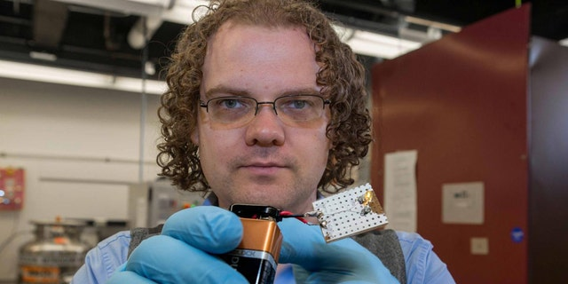 UC graduate student Mark Haase demonstrates the conductivity of carbon nanotube fiber in a battery-powered light.