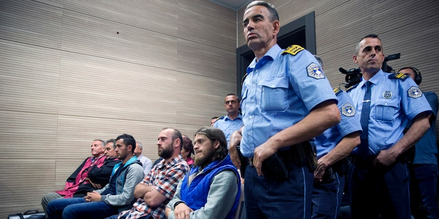 Kosovo police officers stand guard next to from far left, Burim Istrefi, Kenan Plakaj and Arton Ahmeti in court for the foiled attack against the Israeli team in a 2016 qualifying World Cup match in neighboring Albania, in Kosovo's capital Pristina on Friday, May 18, 2018.