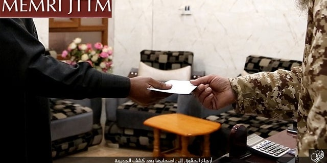 An ISIS detective hands over a reimbursement check to a pharmacy owner who was burglarized.