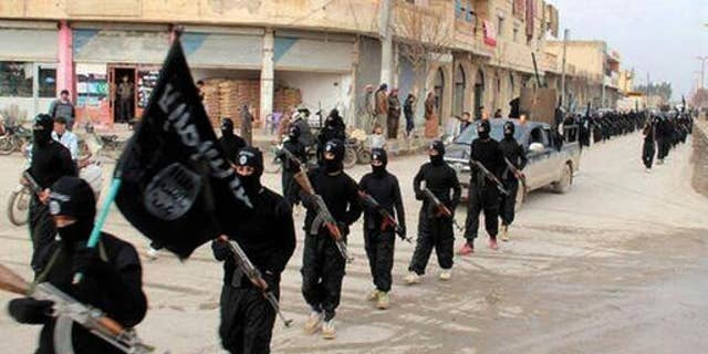 This undated file image posted on a militant website shows fighters from the Islamic State group marching in Raqqa, Syria, Jan. 14, 2014.