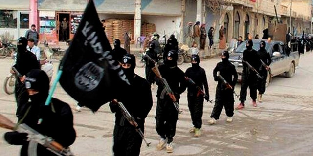 Jan. 14, 2014: This undated file image posted on a militant website on shows fighters from the al-Qaida-linked Islamic State of Iraq and the Levant (ISIS) marching in Raqqa, Syria.
