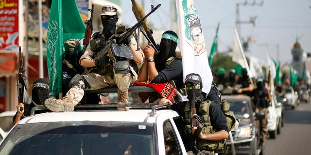 Hamas militants take part in a march through the streets of Gaza City, marking the anniversary of a prisoner swap deal between Israel and Hamas, October 18, 2012.