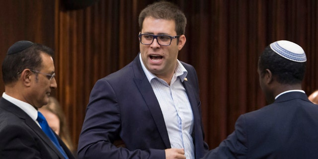 Dan Hazan, a Likud party parliament member, being escorted out by ushers.