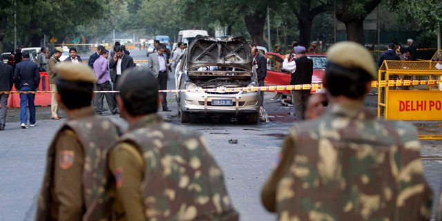 Feb. 13, 2012: Indian policemen watch security and forensic officials examine a car belonging to the Israel Embassy after an explosion tore through that in New Delhi, India.