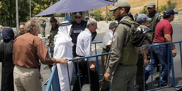 Israeli border police officers stand guard as Palestinians pass a checkpoint near Jerusalem's Old City Friday.