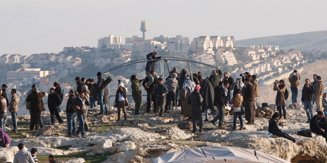 Jan 11, 2013: Palestinians, together with Israeli and foreign activists, stand near newly-erected tents in an area known as E1 at the settlement of Ma'aleh Adumim, near Jerusalem.