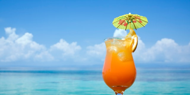 A refreshing drink, with a tropical paradise in the background