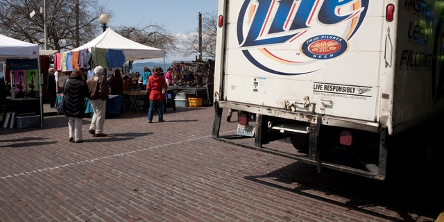Seattle, United States - April 22, 2011: Tourists mill about and around a beer delivery truck.  Brand is Miller Lite. Seattle Pike Place Market, outdoor market crafts stands in the background.