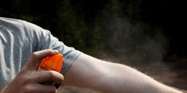 A man is spraying bug spray on his arm.