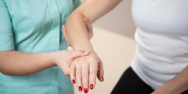 Close-up of pysiotherapist holding woman's forearm