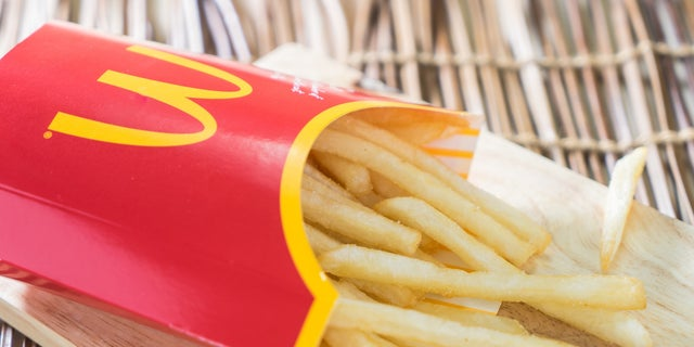 Bangkok, Thailand - September 19, 2015: A box of Mc Donalds French Fries on a wooden tray.