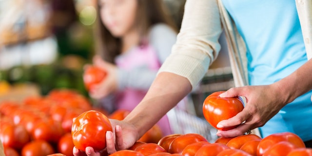 A woman is handling fresh tomatoes at a supermarket or local grocery store. Her daughter is also choosing vegetables in the background, adding depth and context to the image.