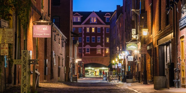 Portland, ME, USA - October 8, 2015: Cobbled Street Lined with shops and Pubs in the Old Port District at night. Portland's Old Port is one of the most successful revitalized warehouse districts in the country. Seamlessly connected to the waterfront, the Old Port is both a working waterfront and a local shopping, dining, residential, and entertainment district.