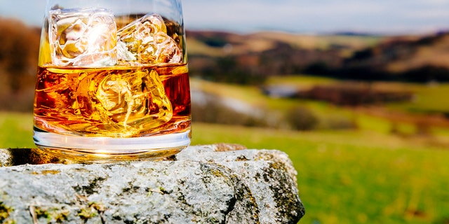 Glass of whisky on the rocks, literally and metaphorically, outdoors in the Scottish Highlands AdobeRGB colorspace.