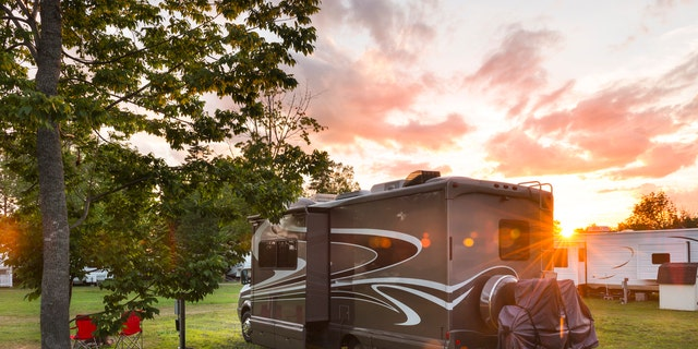 Road trip in motor home. North America. Motor home, camping at sunset. Lens flare.