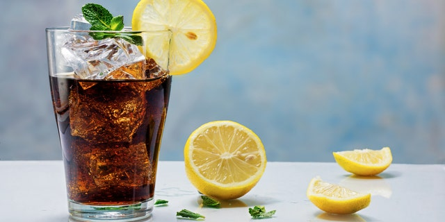 glass of cola or ice tea with ice cubes, lemon slice and peppermint garnish, against a blue wall