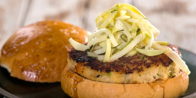 Crab cake sandwich on bun with cabbage garnish on plate sitting on white wooden table top.