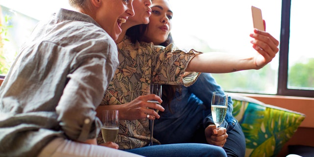 Mixed race girlfriends with Aboriginal woman taking selfie at bar