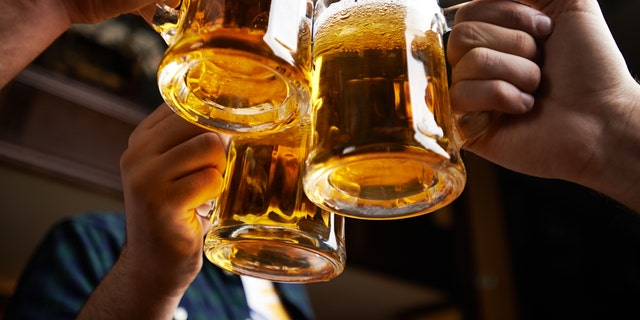 Hands of three men toasting with beer