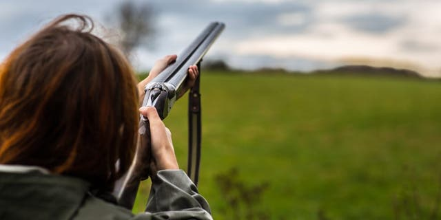 A girl tries her hand at skeet shooting.